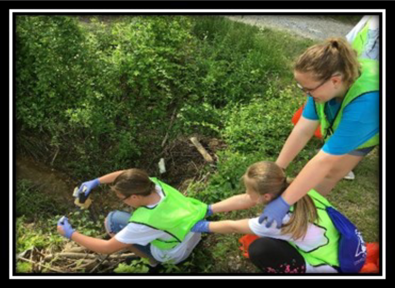 4-H Day Of Service Scott County- Cleaning up garbage near a creek.