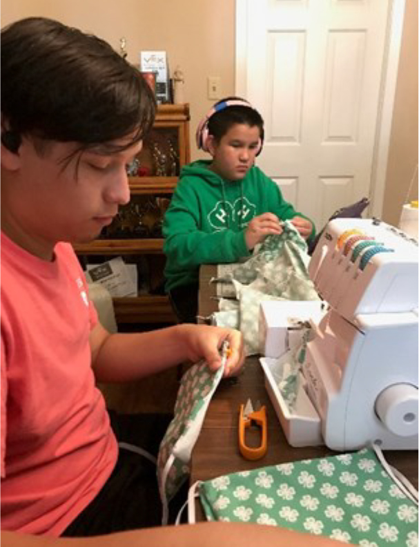 Tow Madison County 4-H'ers cutting and sewing material for COVID 19 masks