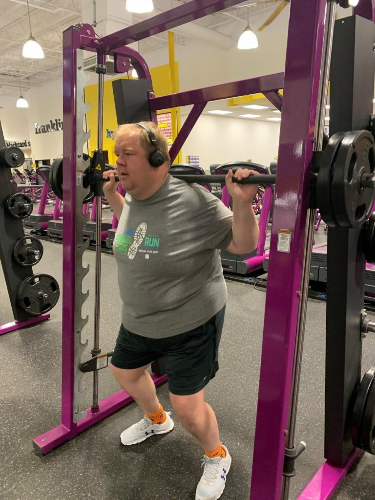 Mr. Crowe in a gym lifting heavy weights.