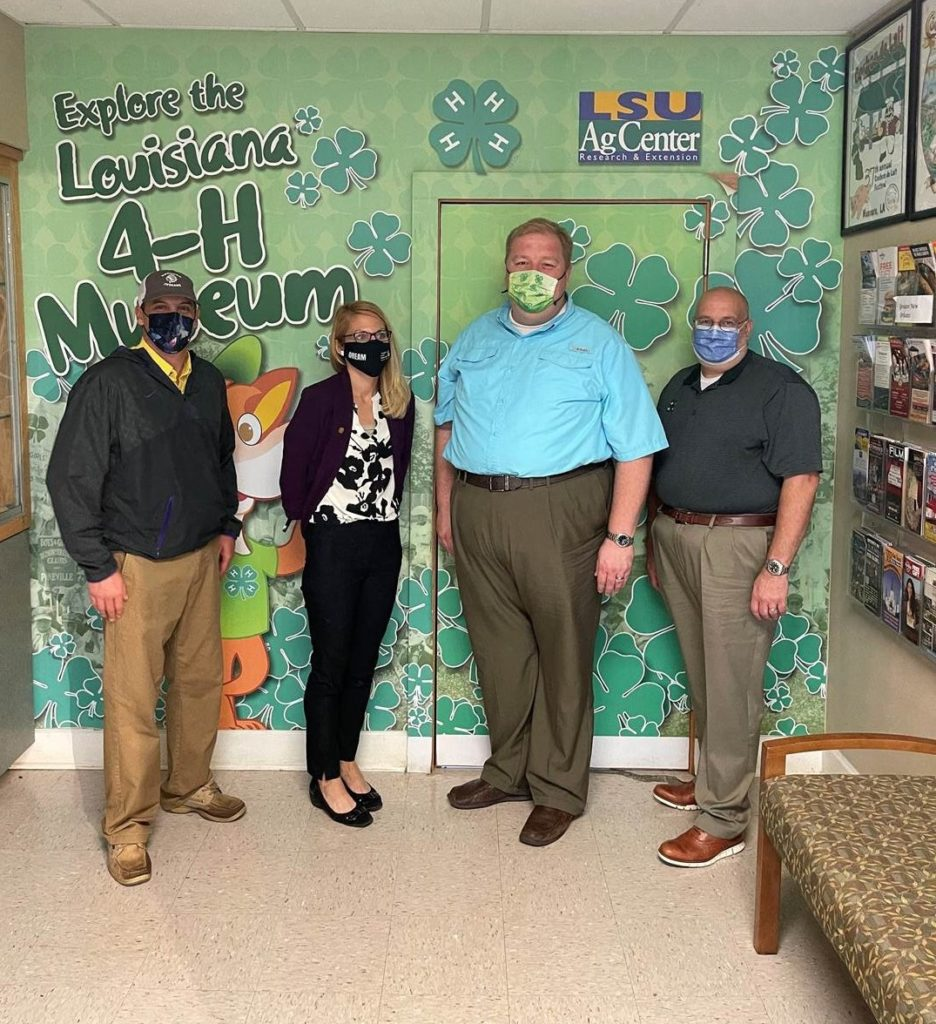 """Mr. Justin Crowe standing with 3 members of the Louisiana 4-H staff against a clover mural that says """"Explore the Louisiana 4-H Museum."""""""